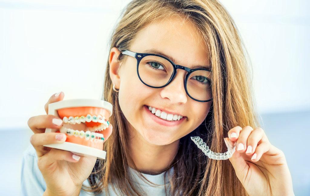 歯の模型とマウスピースを持つ女性
